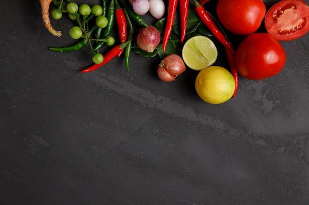 暗い背景で調理する野菜とスパイス Premium写真