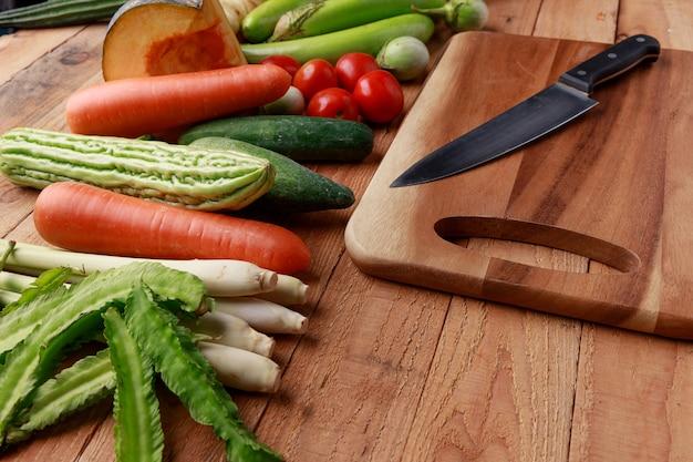 Различные овощи и ингредиенты с ножом и разделочной доской Premium Фотографии