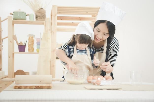 母と娘が台所の部屋でケーキを作るために一緒に調理します。 Premium写真