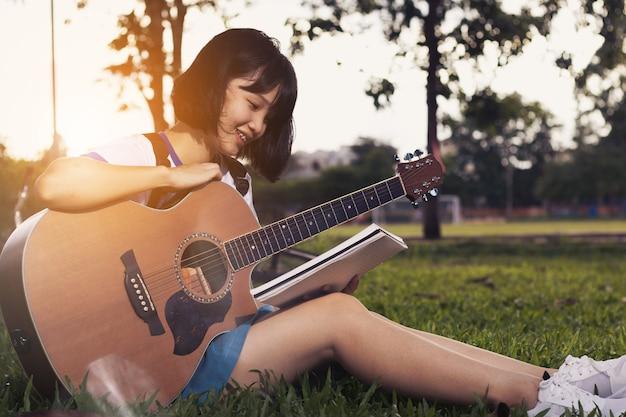 素敵なアジアの十代の女の子が自由時間でリラックスしてギターを弾いています。 Premium写真