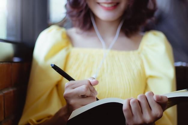 アジアの女性が仕事をして幸せに音楽を聴きます。 Premium写真