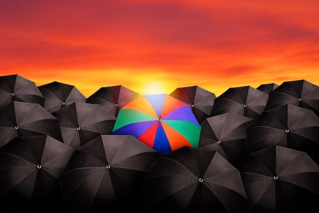 Красочный зонтик в массе черных зонтов. Premium Фотографии