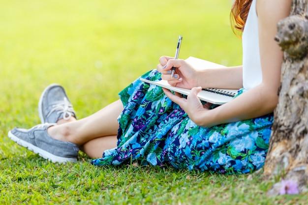 外の芝生の上のノートに書くペンで女性の手 Premium写真