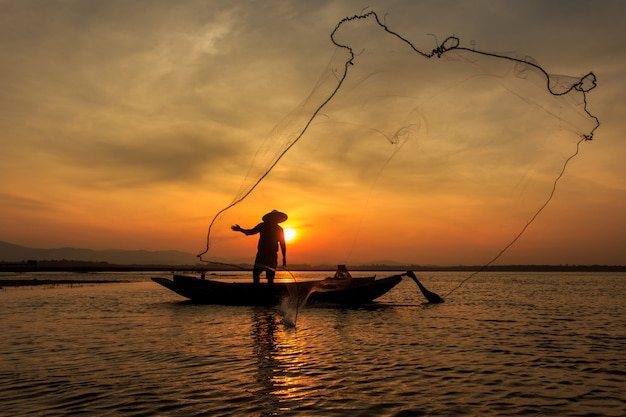 日の出時、ミャンマーで純釣りインレー湖を投げる伝統的な漁師のシルエット Premium写真
