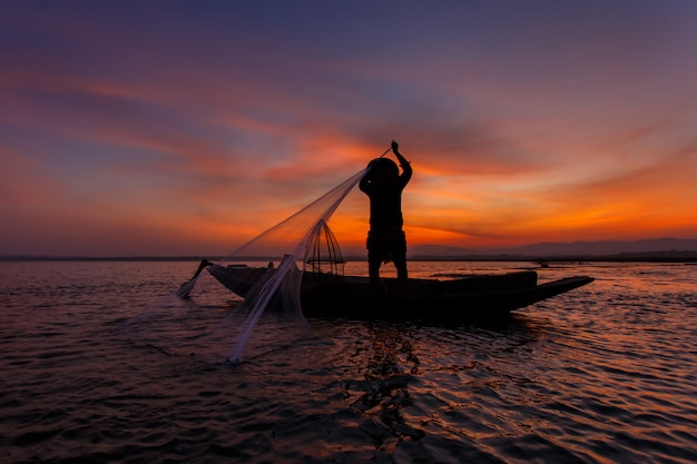 Силуэт традиционных рыбаков, бросая рыболовную сеть озера инле во время восхода солнца, мьянма Premium Фотографии