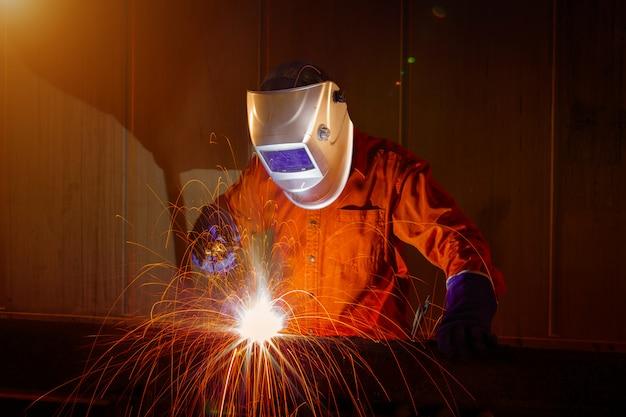 産業用倉庫で防護マスク溶接金属を持つワーカー。 Premium写真