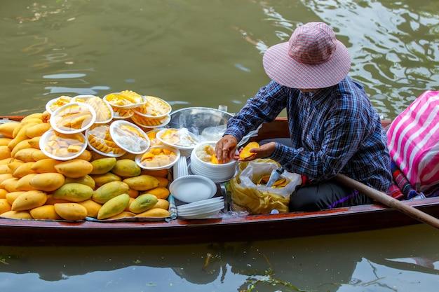 マンゴーをはがしてアジアの女性は販売のためのタイのデザートです。 Premium写真