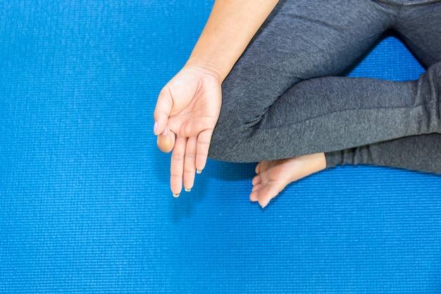 Вид сверху привлекательная молодая женщина работает дома, делая упражнения йоги на синий коврик Premium Фотографии