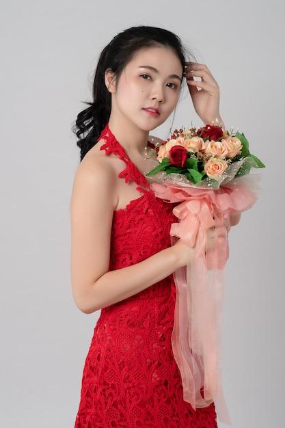 白の手で花の花束と赤いドレスを着ている美しいアジアの花嫁の肖像画 Premium写真