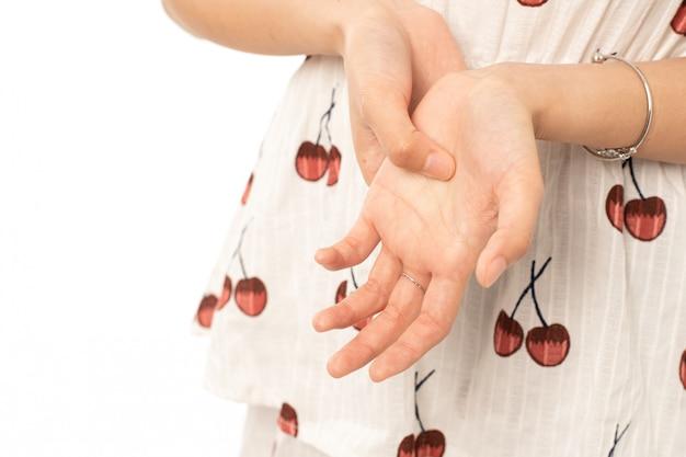 Портрет больной азиатской женщины страдая от пускового пальца на белой предпосылке; самка массирует свою болезненную руку от симптомов периферической невропатии. Premium Фотографии