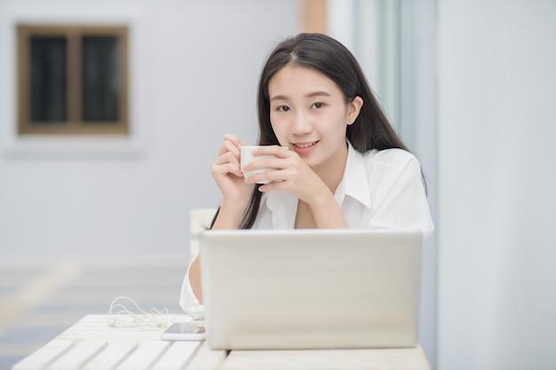 Портрет милой азиатской женской модели использует портативный компьютер для онлайн-общения; счастливый бизнес женщина пить кофе, сидя на белом столе. Premium Фотографии