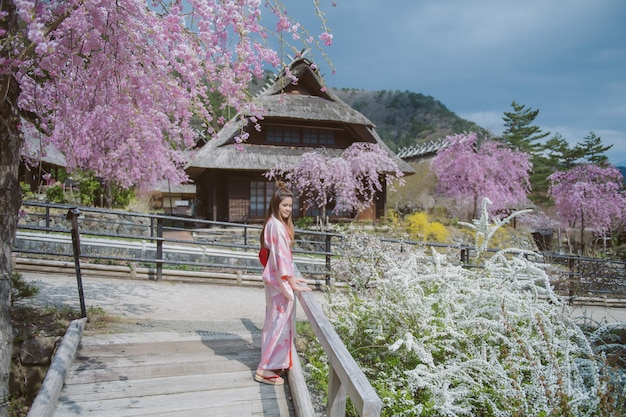 日本の桜と伝統的な日本の着物を着ているアジアの女性。 Premium写真
