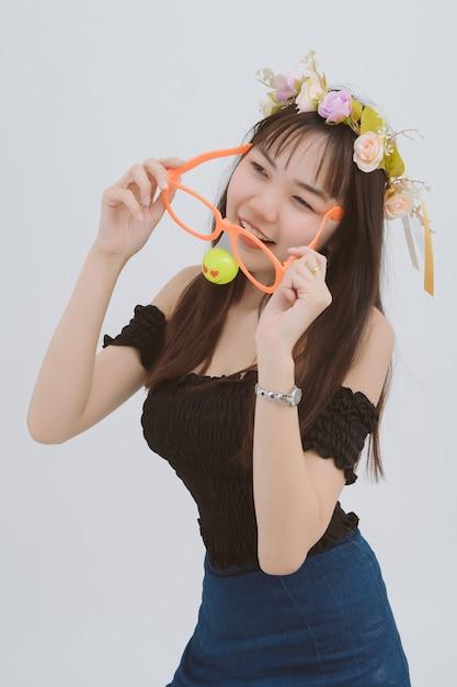 グレーに分離された大きなメガネの女性。スタジオで幸せと面白いアジアの少女の肖像画。 Premium写真