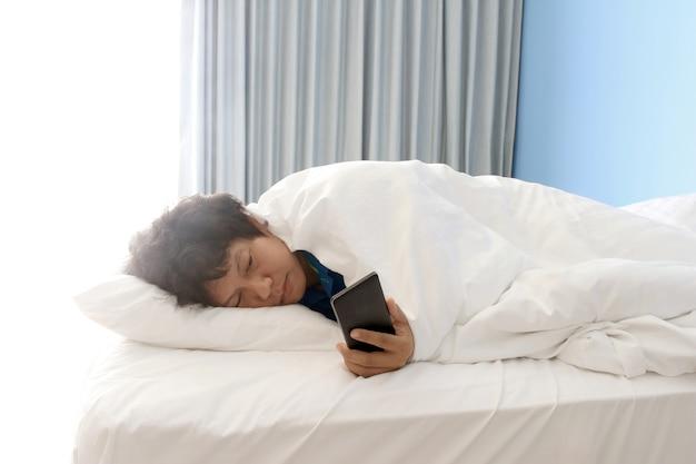 ベッドで寝てスマートフォンを持っている男 Premium写真