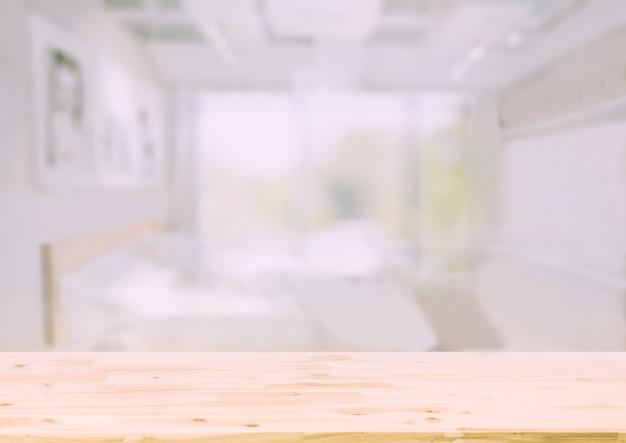 Деревянная столешница перед размытым фоном интерьера спальни Premium Фотографии