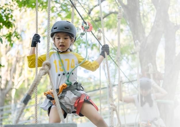 Счастливая школьница наслаждается деятельностью в парке приключений Premium Фотографии