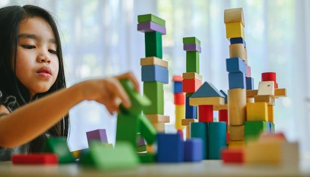 Маленькая девочка играет со строительными игрушечными блоками Premium Фотографии