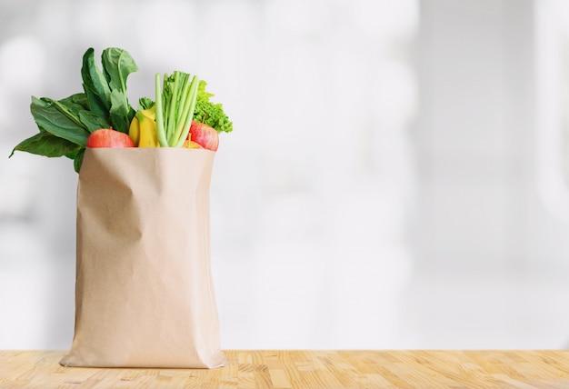 Бумажный пакет со здоровой пищей на белом фоне Premium Фотографии