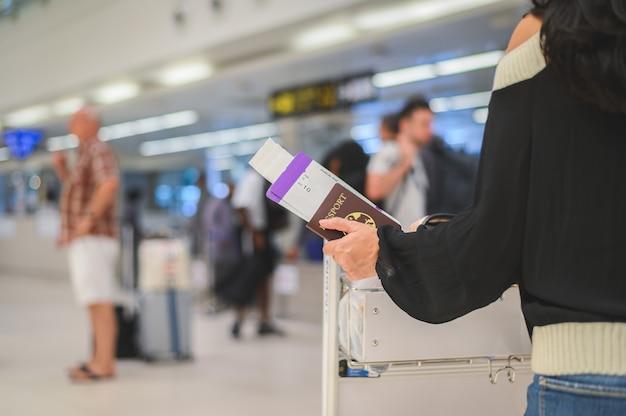 Крупным планом девушки с паспортами и посадочный талон в аэропорту Premium Фотографии