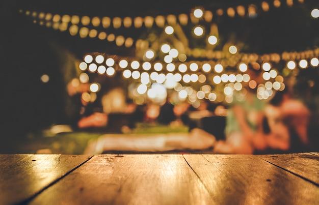 Изображение деревянного стола перед абстрактным размытым фоном ресторан огни Premium Фотографии