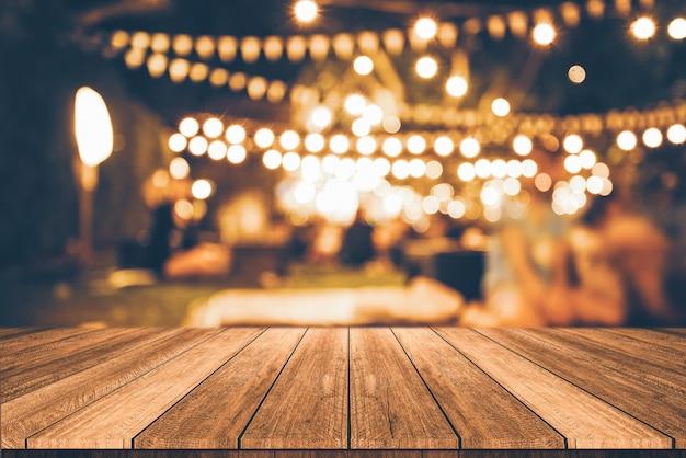 Деревянный стол перед абстрактным размытым фоном ресторан огни Premium Фотографии