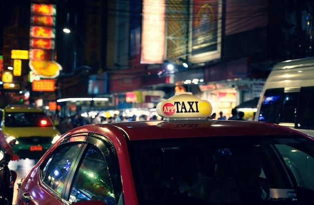 Такси знак с расфокусированным огни размытия в китайском квартале в бангкоке в ночное время, таиланд, юго-восточная азия Premium Фотографии