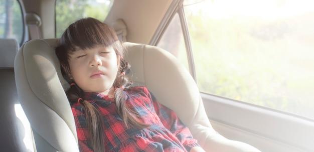 Азиатская маленькая девочка спит в машине с автокреслом Premium Фотографии