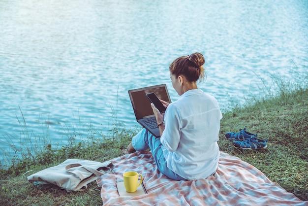 川の隣に座っている女性 Premium写真