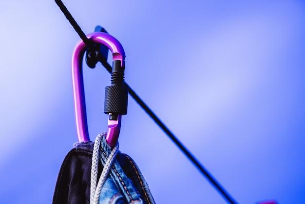 ロープとカラビナパープルとブラックハンギングジーンズ。 Premium写真