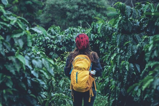 バックパックを持つ少女は立って、コーヒーガーデンを歩いています。旅行リラックス Premium写真