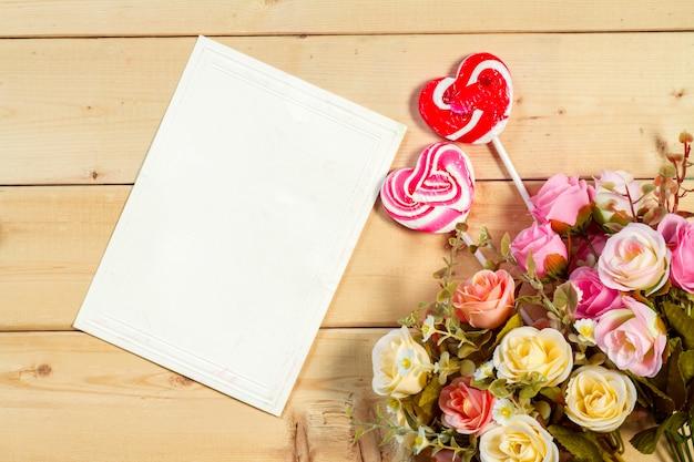 バラの花と木製の背景にハート形のお菓子とテキストの空のタグ Premium写真