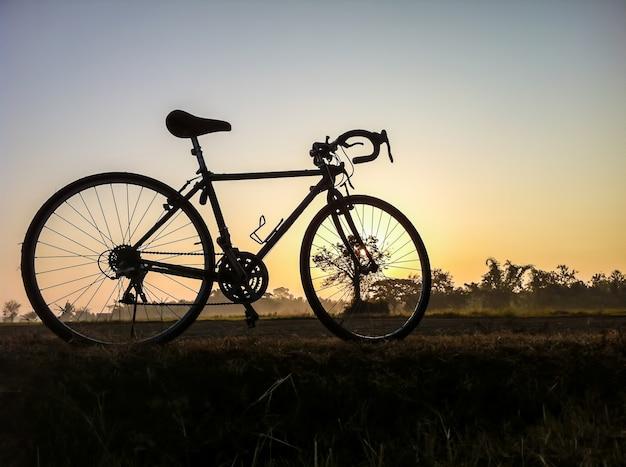 Велосипед на сельской соломенной местности с силуэтом утреннего света и винтаж Premium Фотографии