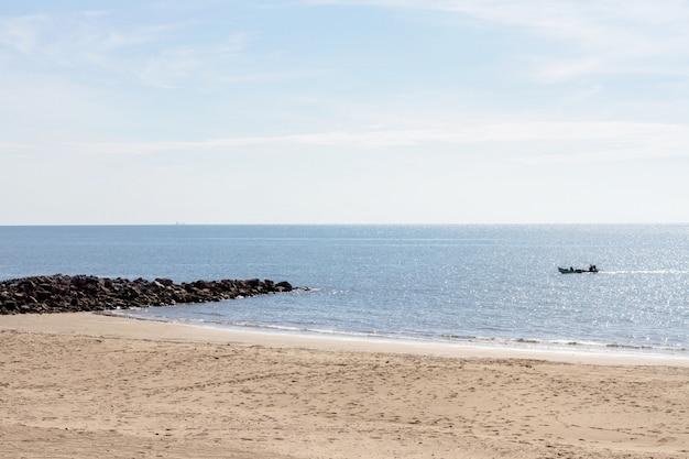 夏の朝に海とビーチで漁船 Premium写真