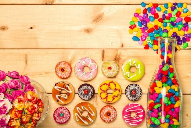 甘いドーナツと瓶の中のカラフルなジェリービーンズ Premium写真