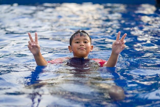 夏にはスイミングプールで泳いでいる幸せなアジア子供男の子 Premium写真