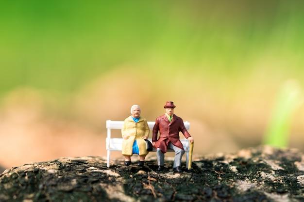 仕事の退職と保険の概念として使用して白いベンチに座っているミニチュア高齢者 Premium写真
