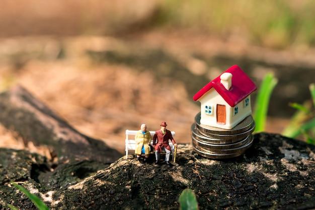 仕事の退職と家族の概念として使用してスタックコインにミニ家で座っているミニチュア高齢者 Premium写真