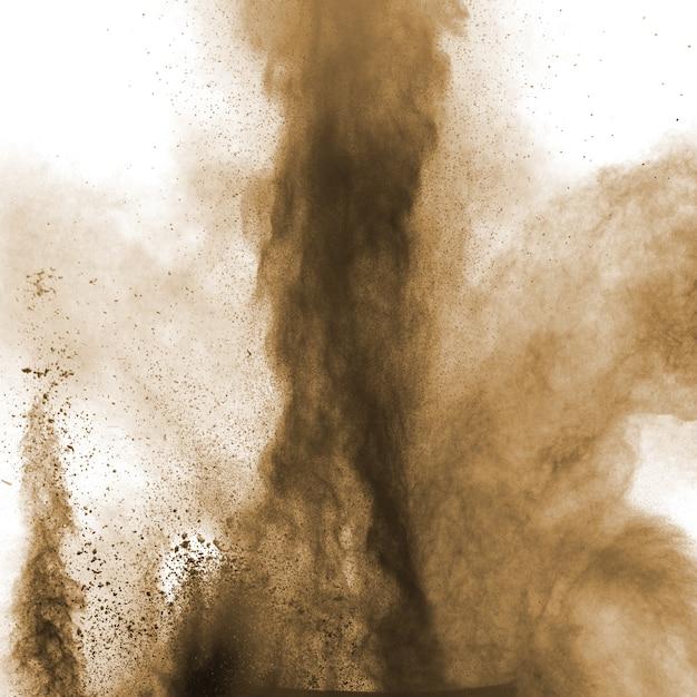 白い背景の上の爆発性の茶色の粉。 Premium写真