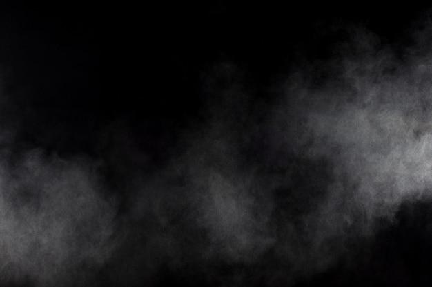 黒の背景に抽象的な煙。白い煙雲。 Premium写真