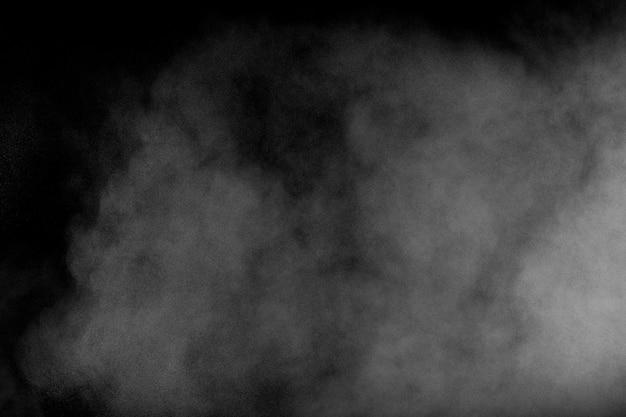 Белая пыль выдыхается в воздухе. порошок движения взрыва в темном фоне. Premium Фотографии