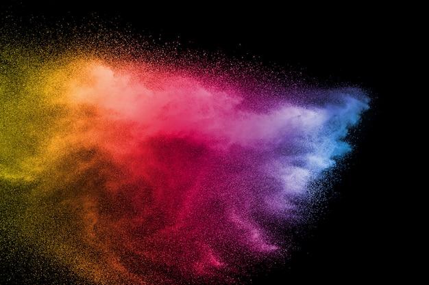 Взрыв цветной порошок на черном фоне. всплеск цветной порошок пыли на темном фоне. Premium Фотографии