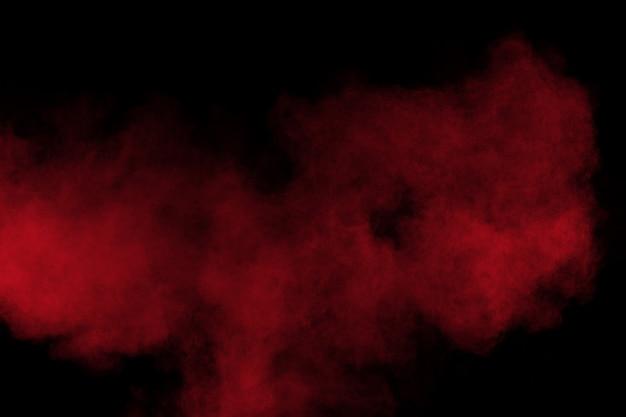 Взрыв порошка красного цвета на черной предпосылке. заморозить движение всплеска частиц красной пыли. Premium Фотографии