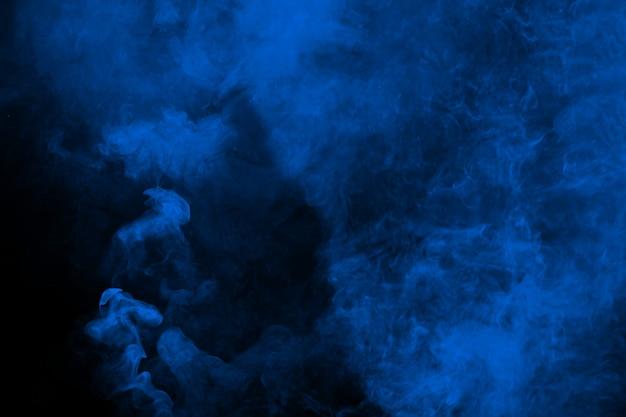 黒の背景に抽象的な青い煙。 Premium写真