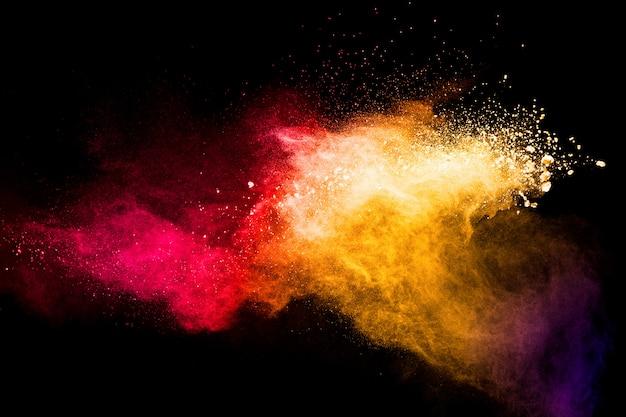 Красный желтый порошок взрыва облака на черном фоне. заморозьте движение брызг частиц пыли красного желтого цвета. Premium Фотографии
