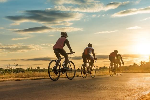 日没時に自転車に乗っている男性のシルエットグループ。 Premium写真
