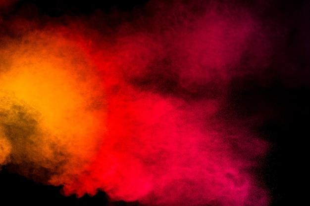 Абстрактный желтый оранжевый порошок взрыв на черном фоне. движение замораживания желтый оранжевый всплеск частиц пыли. Premium Фотографии