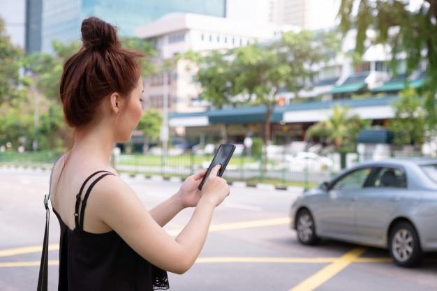 若い美しい女性がシンガポールでタクシーをつかむために電話を使用しています。道路の横に立っている Premium写真