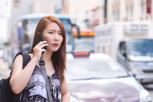 Молодая красивая женщина, вызов общественного такси по телефону в сингапуре. стоя рядом с дорогой Premium Фотографии