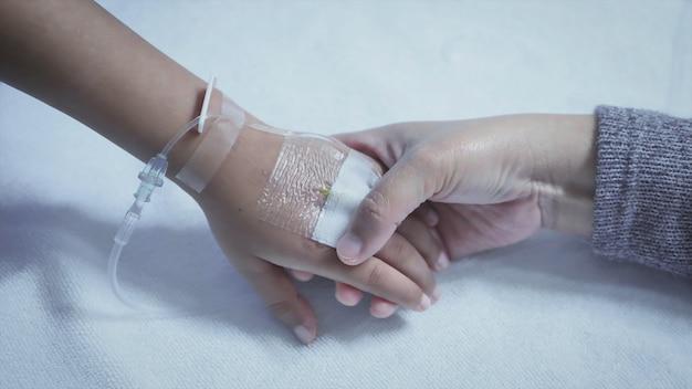 病院で彼の息子の病気のベッドの手を握って母。手を触れます。介護促進 Premium写真