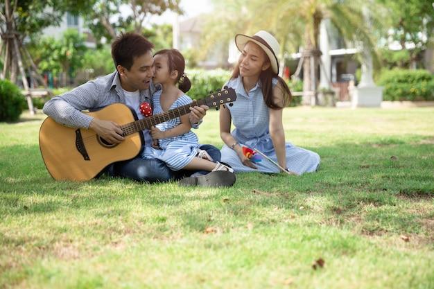 アジアの幸せな家族。父、母と娘が自然の日差しの下で公園でキスをします。家族休暇の概念。 Premium写真